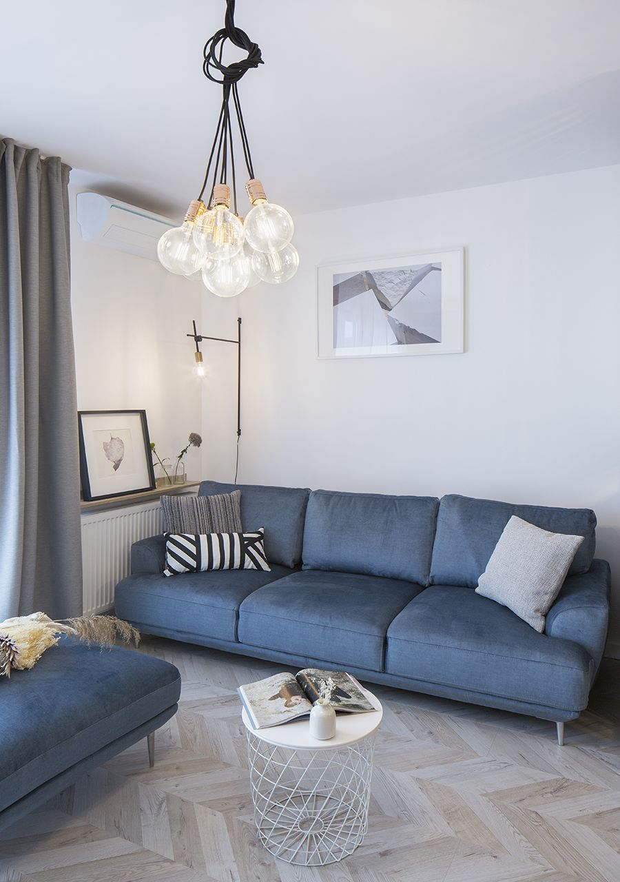 Comfy blue sofa in the corner adds colorful charm to the small white living room
