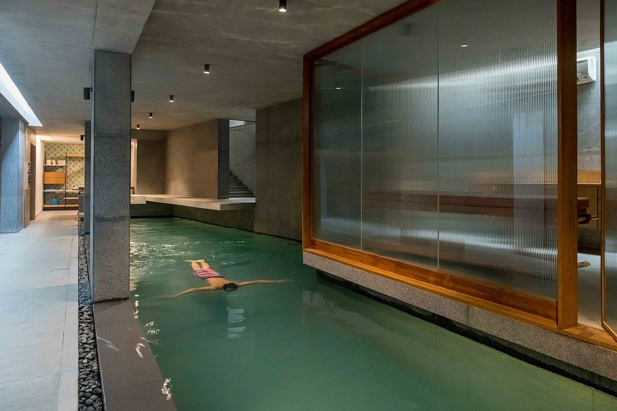 Concrete, granite stone and glass create the new underground level pool and spa at this Indian home