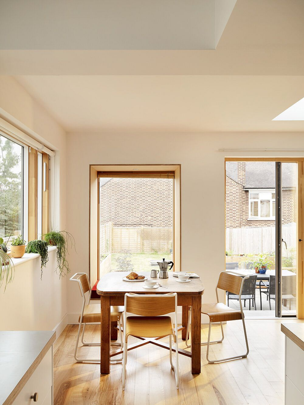 Custom windows and large glass doors bring ample natural light into the dining area and kitchen