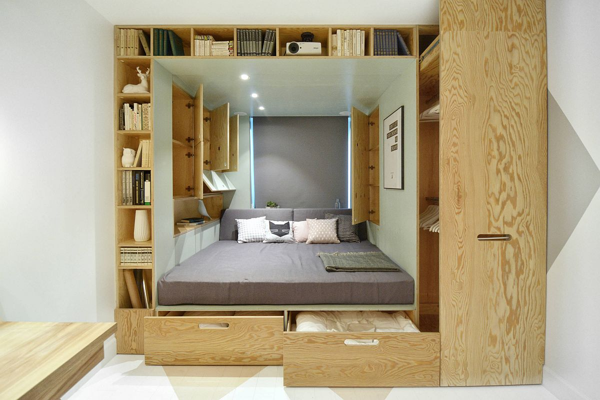 Custom wooden box inside the bedroom niche with ample storage and shelving units also houses the bed