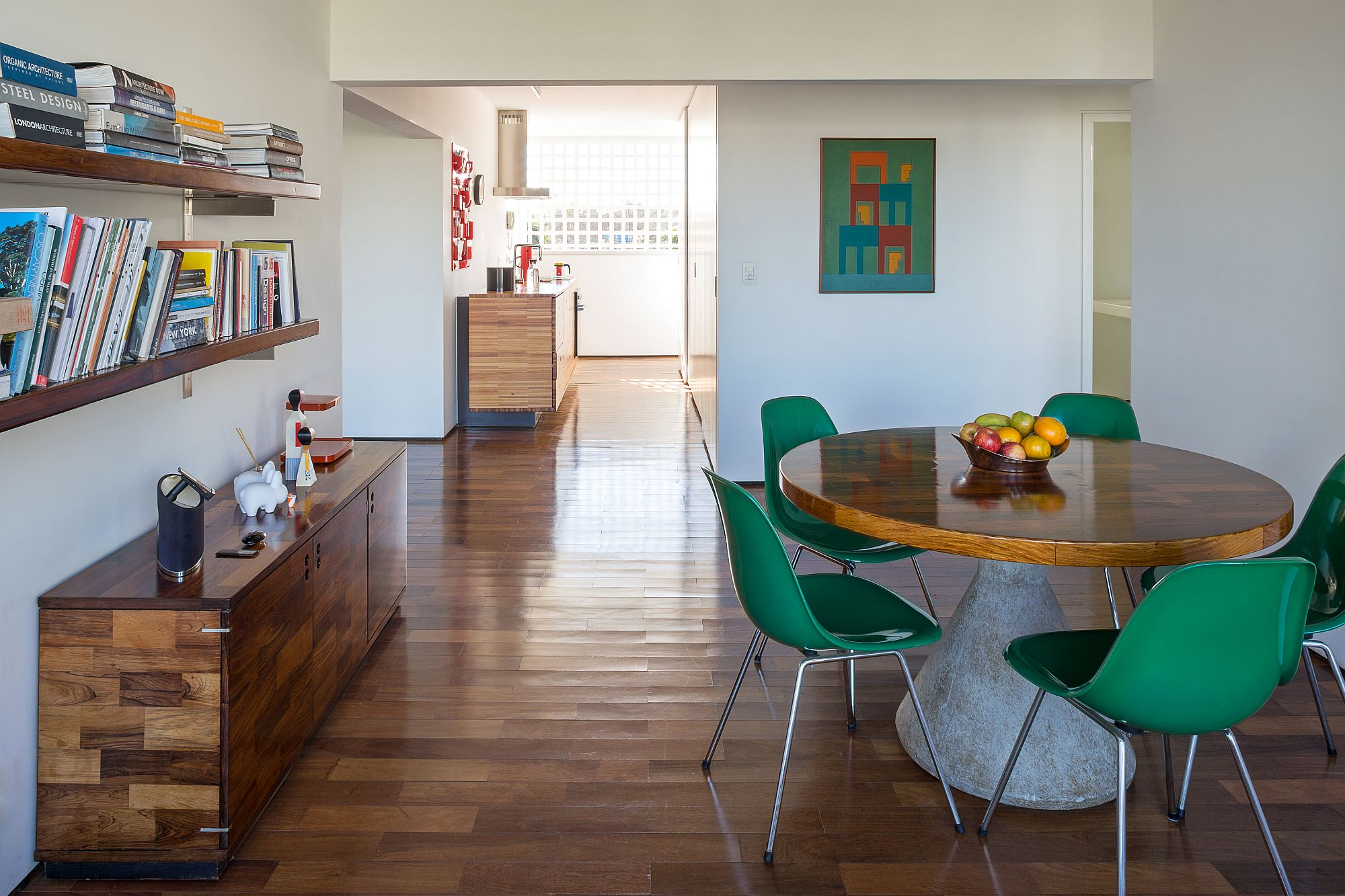 Dining table with concrete base, wooden top is surrounded by beautiful green chairs