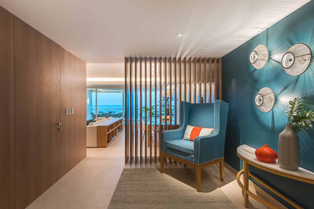 Entry with brilliant accent wall in aqua along with fabulous sconce lights makes a big visual impact