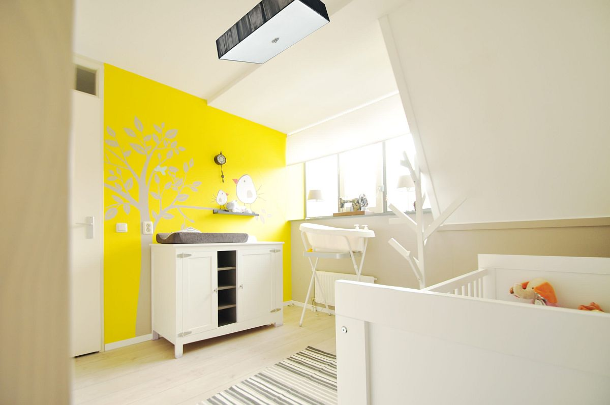 Exquisite white gender-neutral nursery of Amsterdam home with a brilliant yellow accent wall