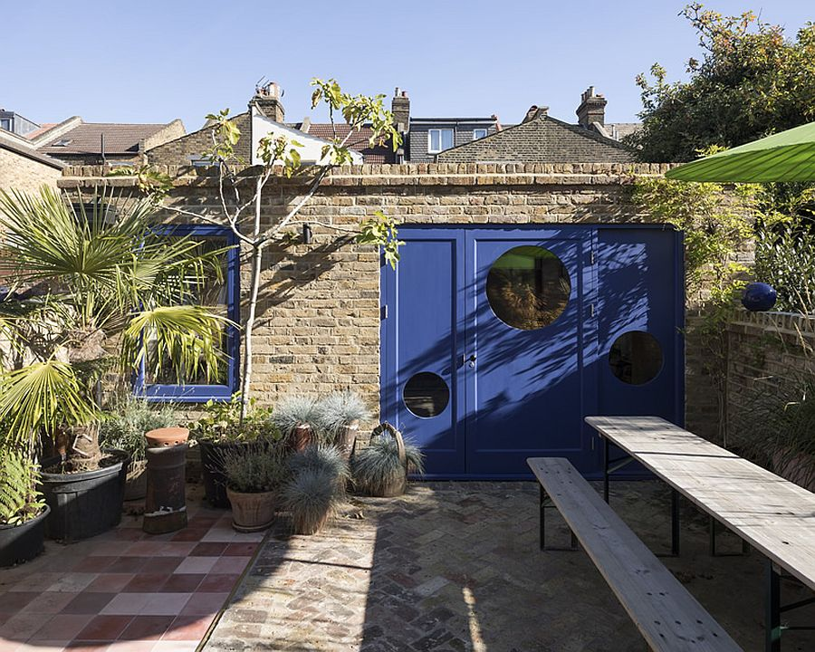 Garden Studio with dashing blue door and window frames separates itself from the main house