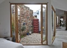 Glass-doors-with-wooden-frame-swing-open-to-connect-the-bedroom-with-the-small-courtyard-outside-81649-217x155