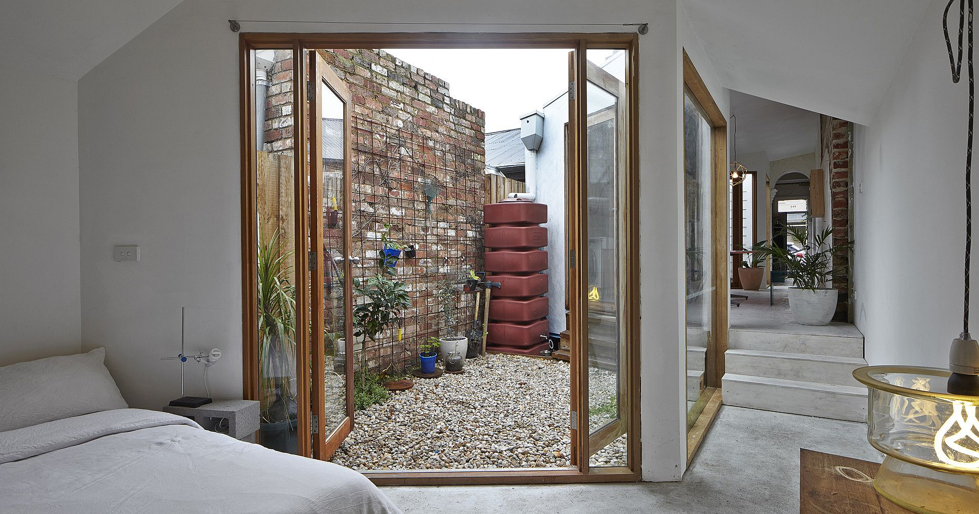 Glass-doors-with-wooden-frame-swing-open-to-connect-the-bedroom-with-the-small-courtyard-outside-81649