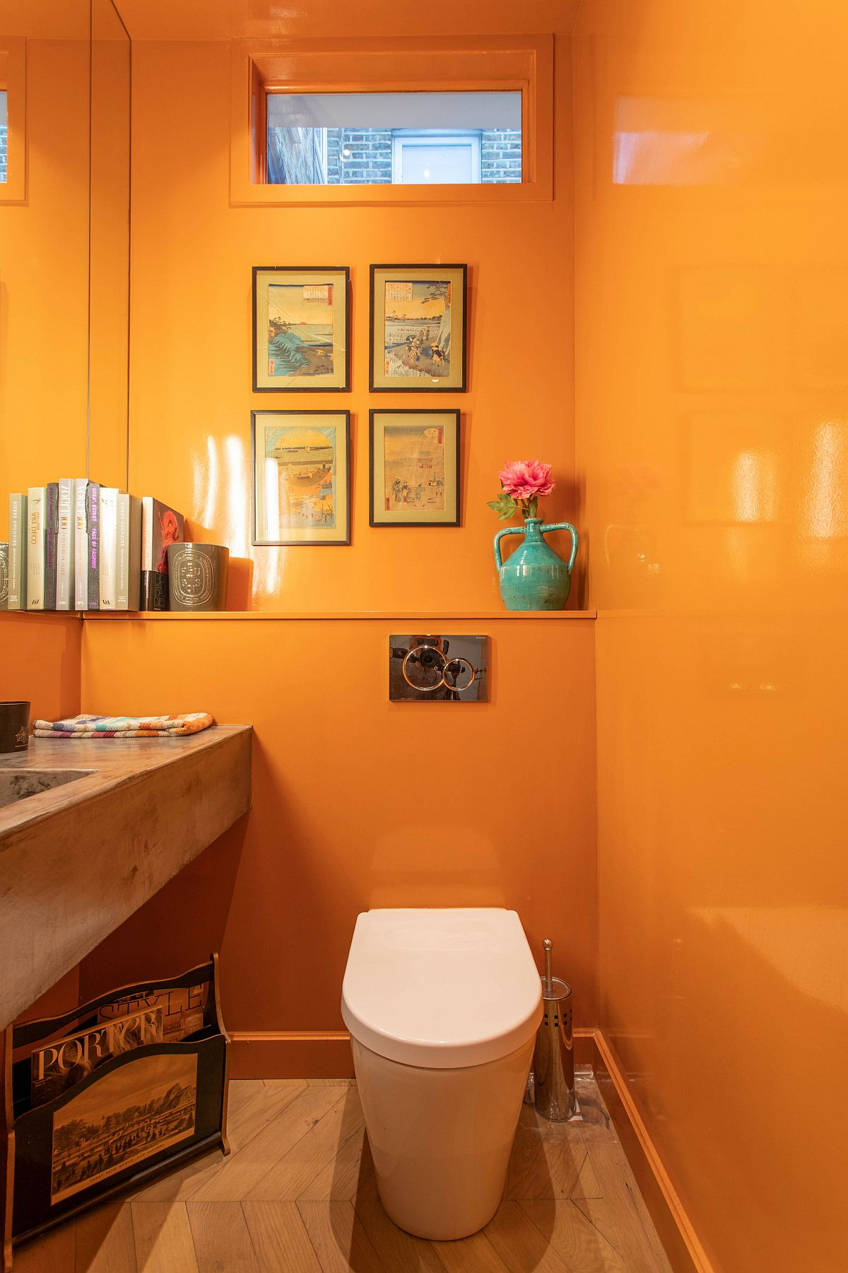 Glossy bathroom walls in orange with a wooden vanity create a light-filled and vivaciou setting