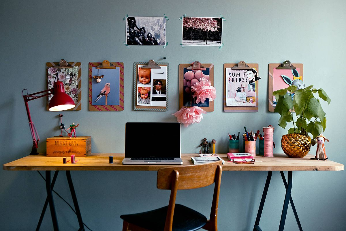 Gorgeous eclectic home office with grayish-blue walls, wall-mounted photographs and clipboards