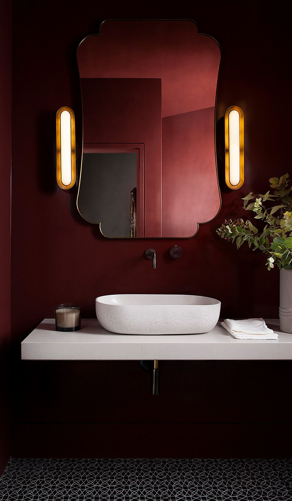 Gorgeous mirror, beautiful sconce lights and deep red walls bring glamor into this contemporary powder room