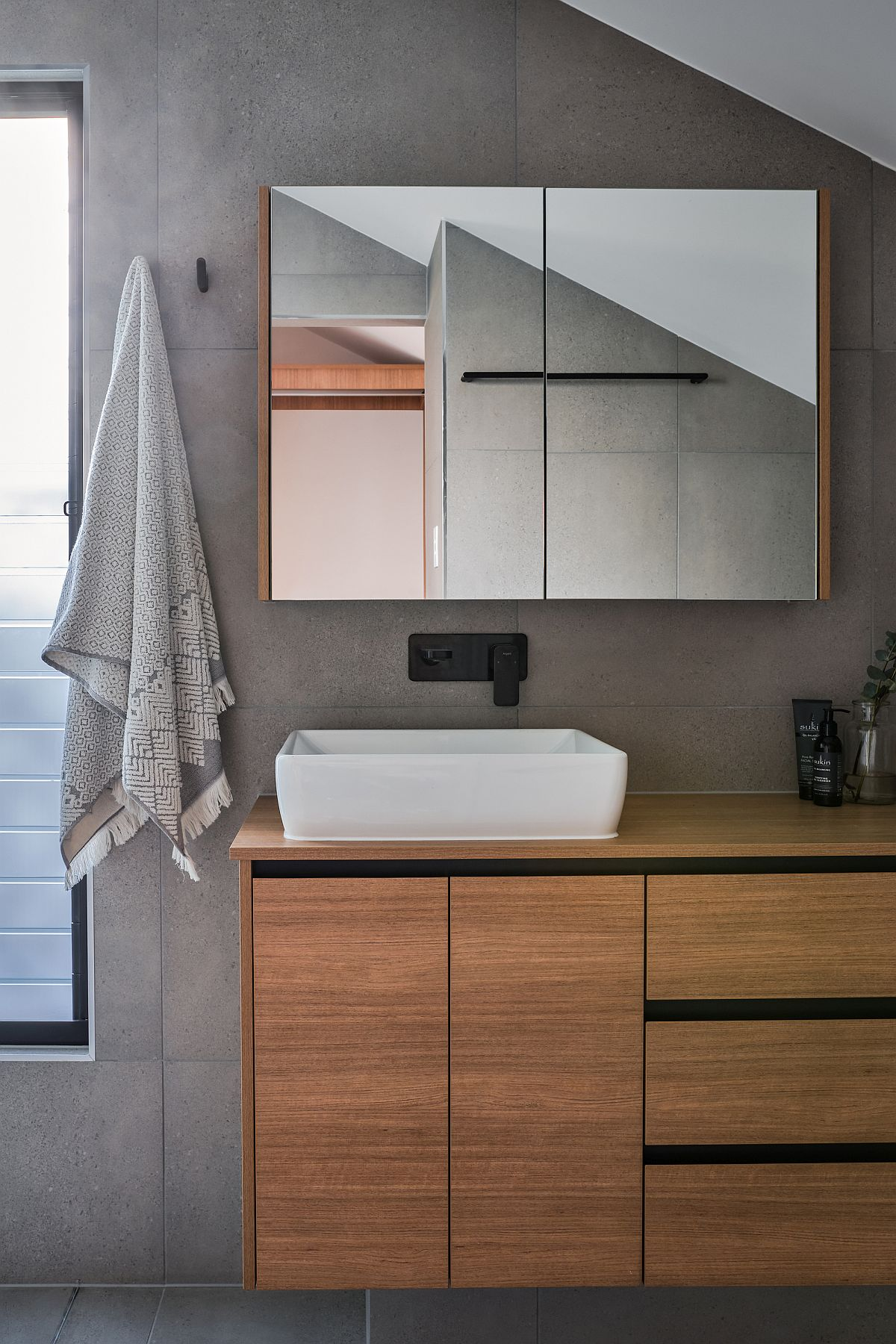 Gray and wood bathroom with an idustrial-minimal style and floating vanity