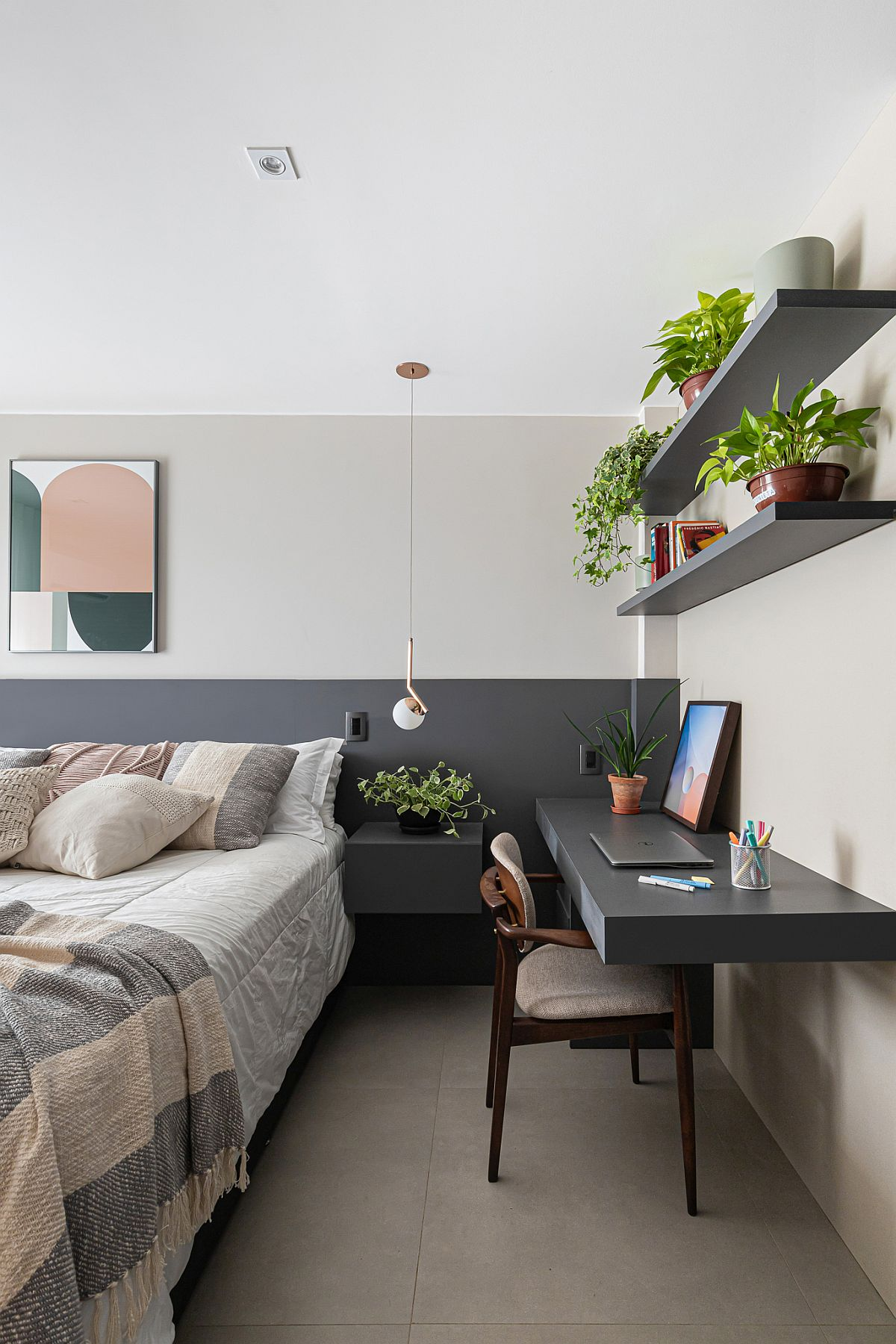 Gray half-wall coupled with gray workspace and slim floating shelves in the small bedroom