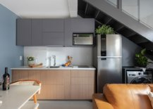 Kitchen-wall-of-the-apartment-under-the-extended-mezzanine-level-with-dark-gray-cabinets-and-refrigerator-and-washing-machine-under-the-staircase-13093-217x155