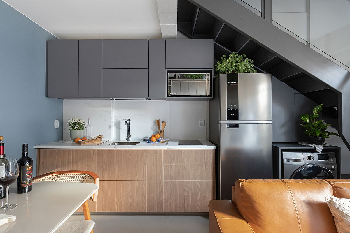 Kitchen wall of the apartment under the extended mezzanine level with dark gray cabinets and refrigerator and washing machine under the staircase