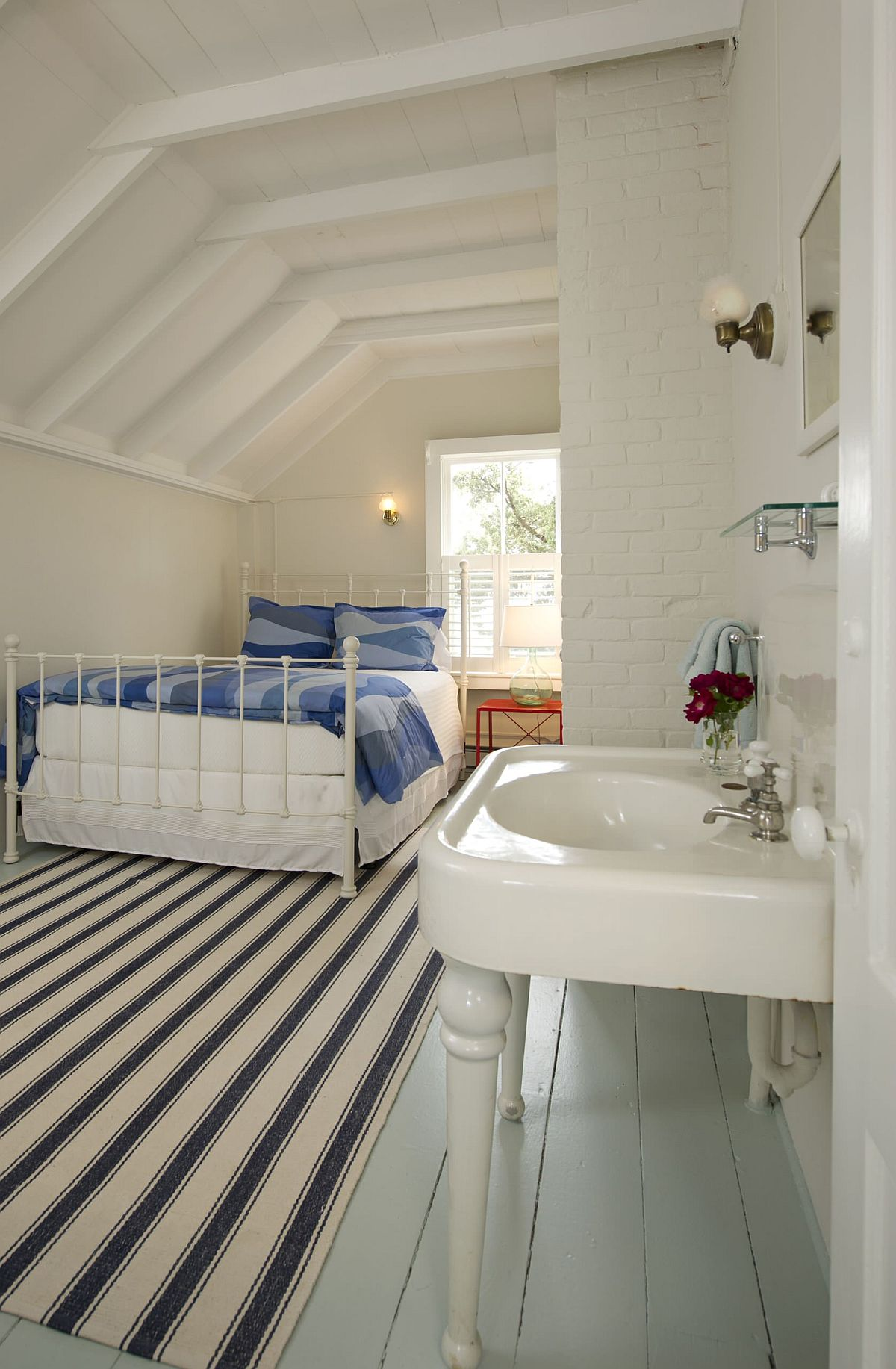 Light blue painted wood floor along with striped rug adds color to the fabulous beach style bedroom