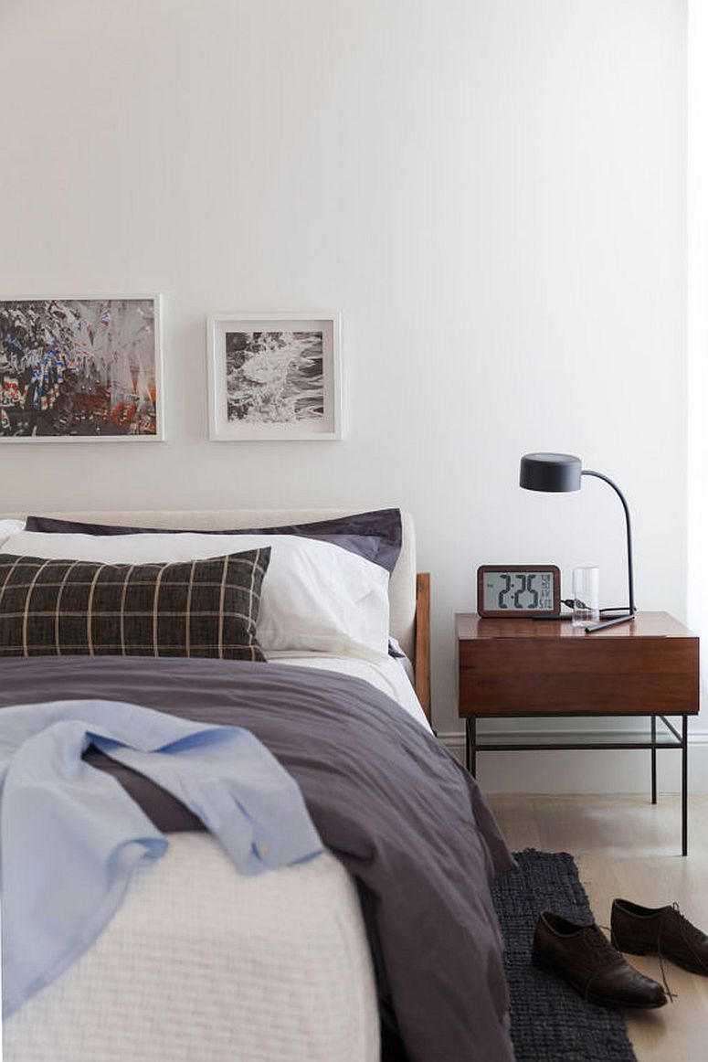 Main bedroom of the apartment in white with a slim and stylish wooden side table
