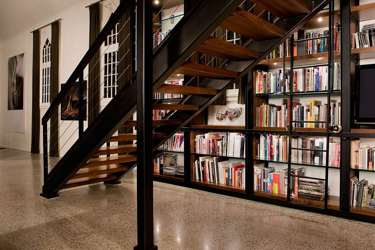 Metal and wood shape custom bookshelf and staircase inside the spacious church turned into loft
