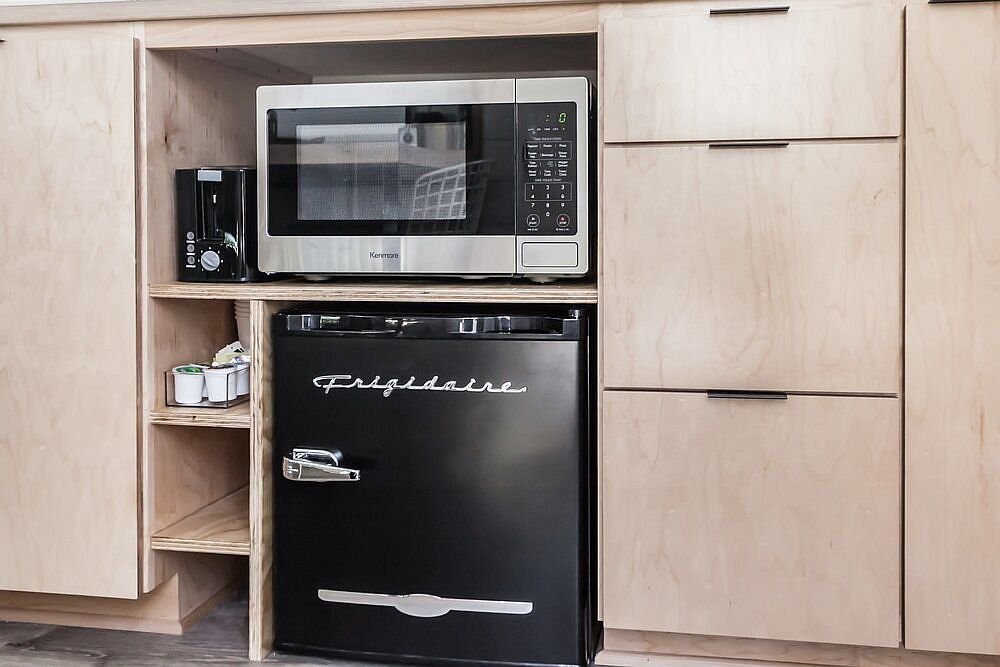 Microwave and small refrigerator inside the tiny kitchen that become a part of the cabinets