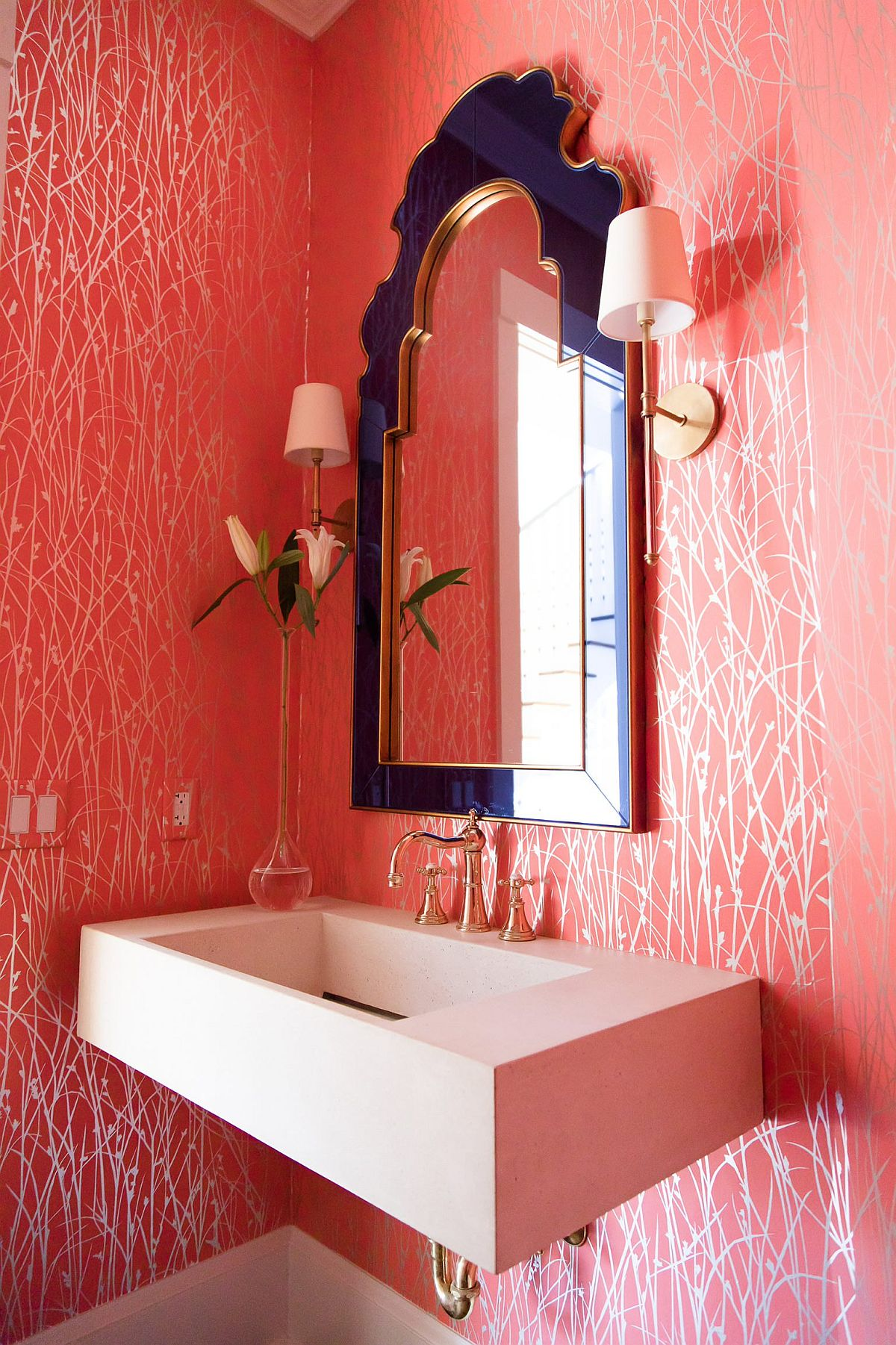 Mirror with purple framed and walls with pattern-filled pink wallpaper are all about glam!