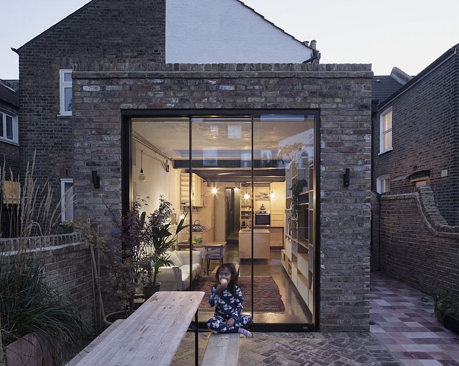 Modern extension of classic brick house in London with glass walls and windows that welcome the outdoors