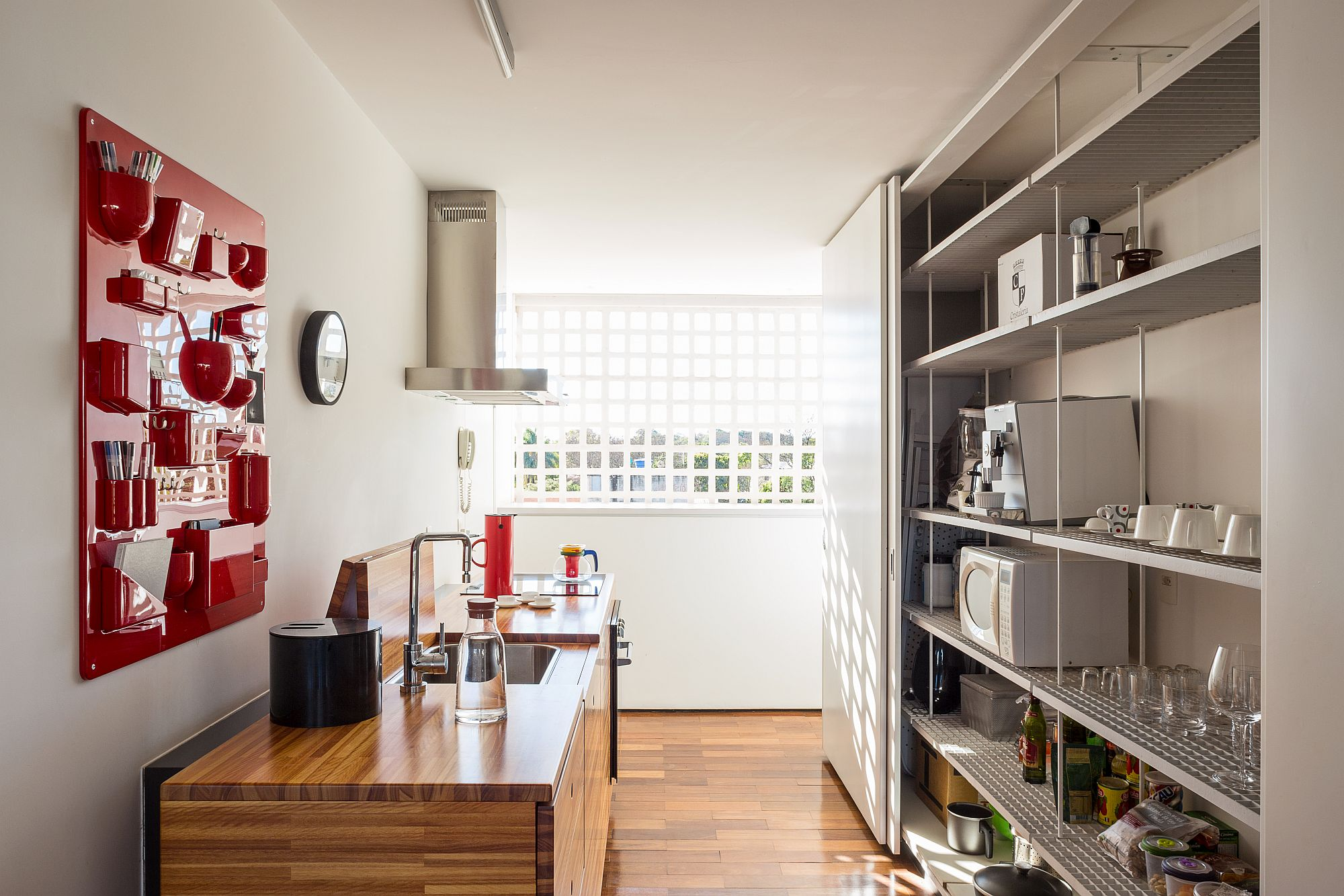 Modern kitchen with red accent storage system and stainless steel shelves