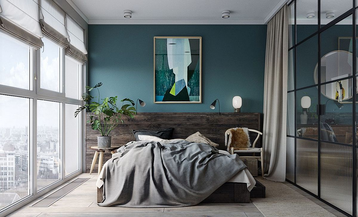 Modern minimal bedroom with bluish-gray accent wall and custom glass walls with adark frame