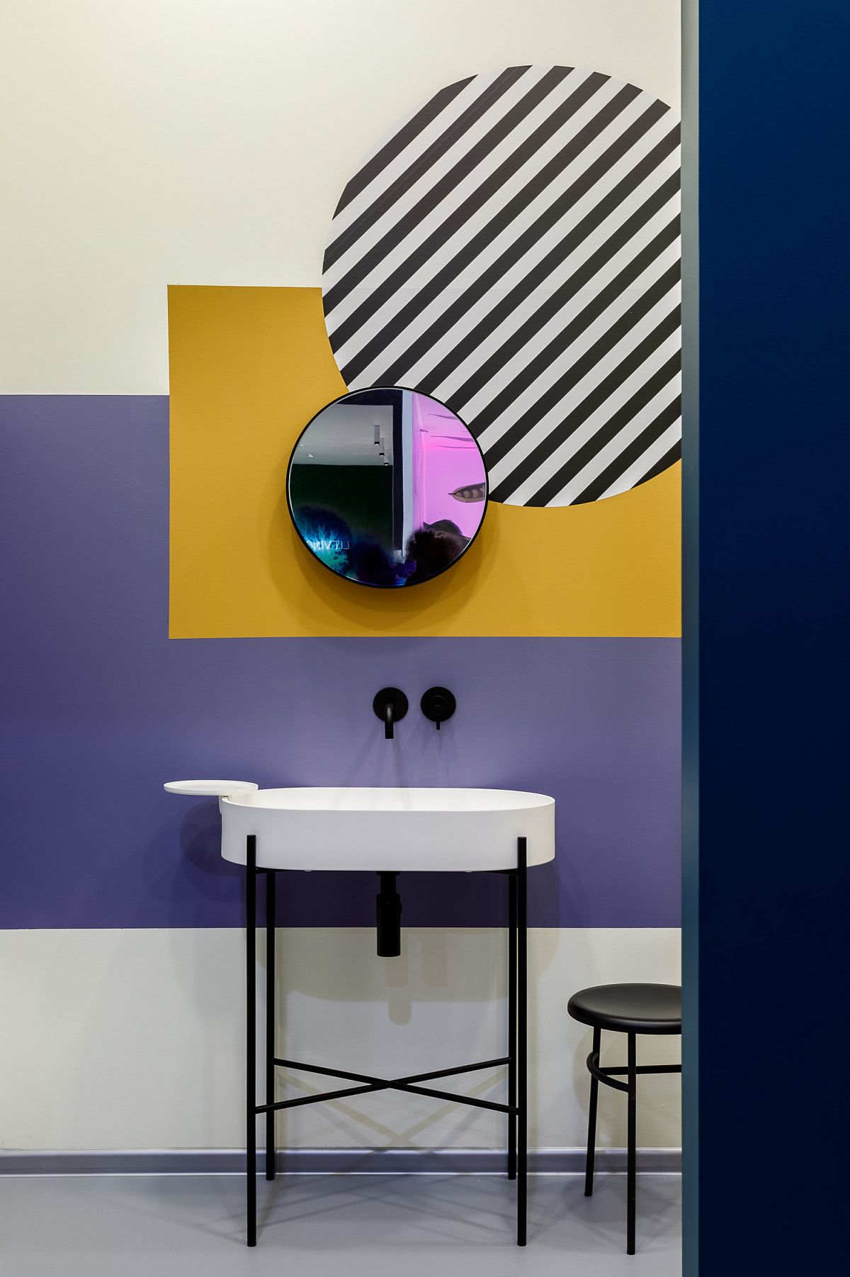 Multiple colors on the wall along with stripes bring certain artistic appeal to this minimal bathroom