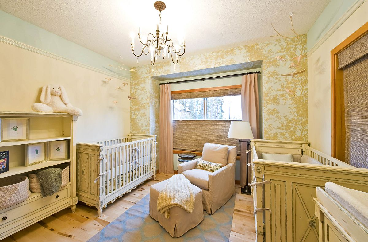 Nursery in mellow yellow with whimsical, tree-patterned wallpaper in the backdrop that is eye-catching