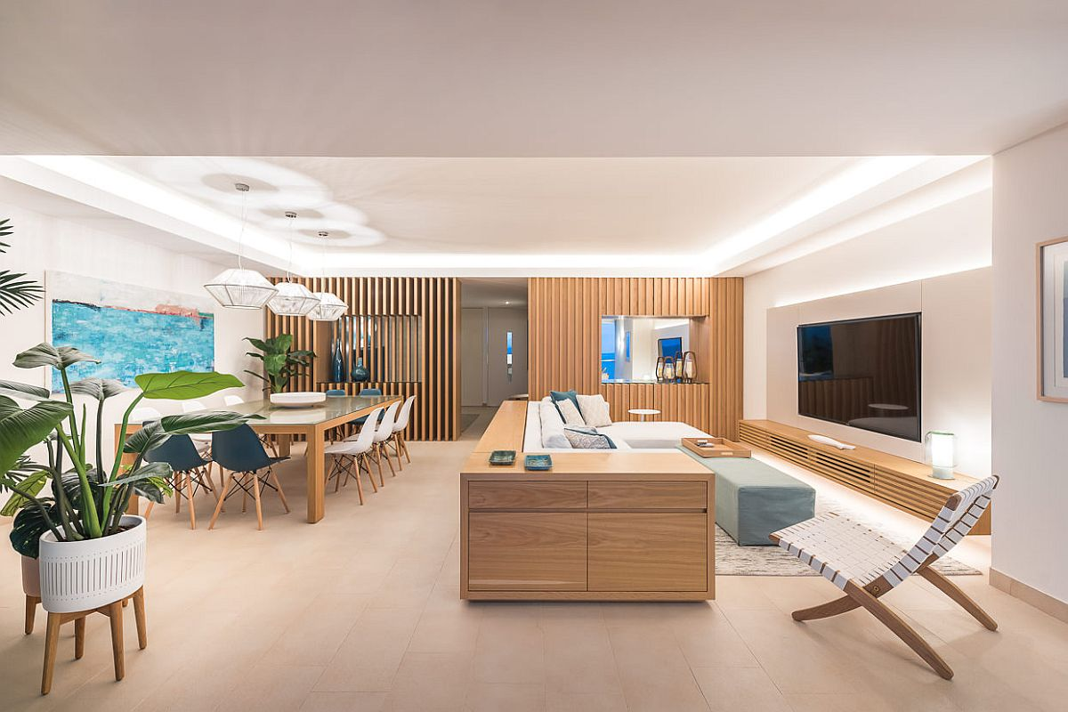 Open-plan-living-area-of-the-home-in-neutral-colors-along-with-bright-blue-accents-and-even-lighting-49673