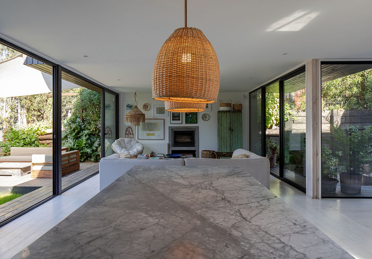 Open plan living area of the house with kitchen and dining space along with patios on both ends