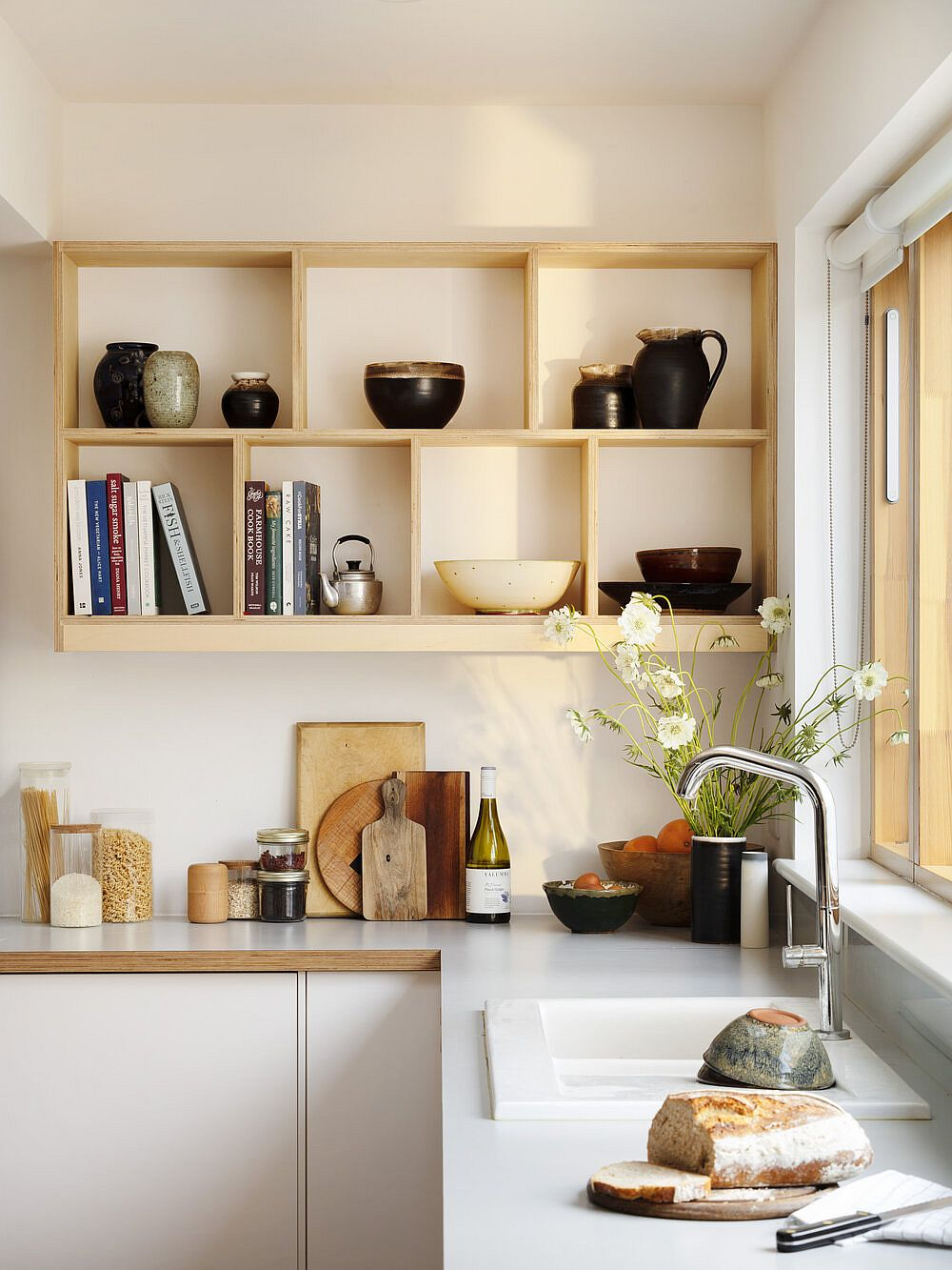 Open shelves in the corner create an eye-catching display in the modern white kitchen