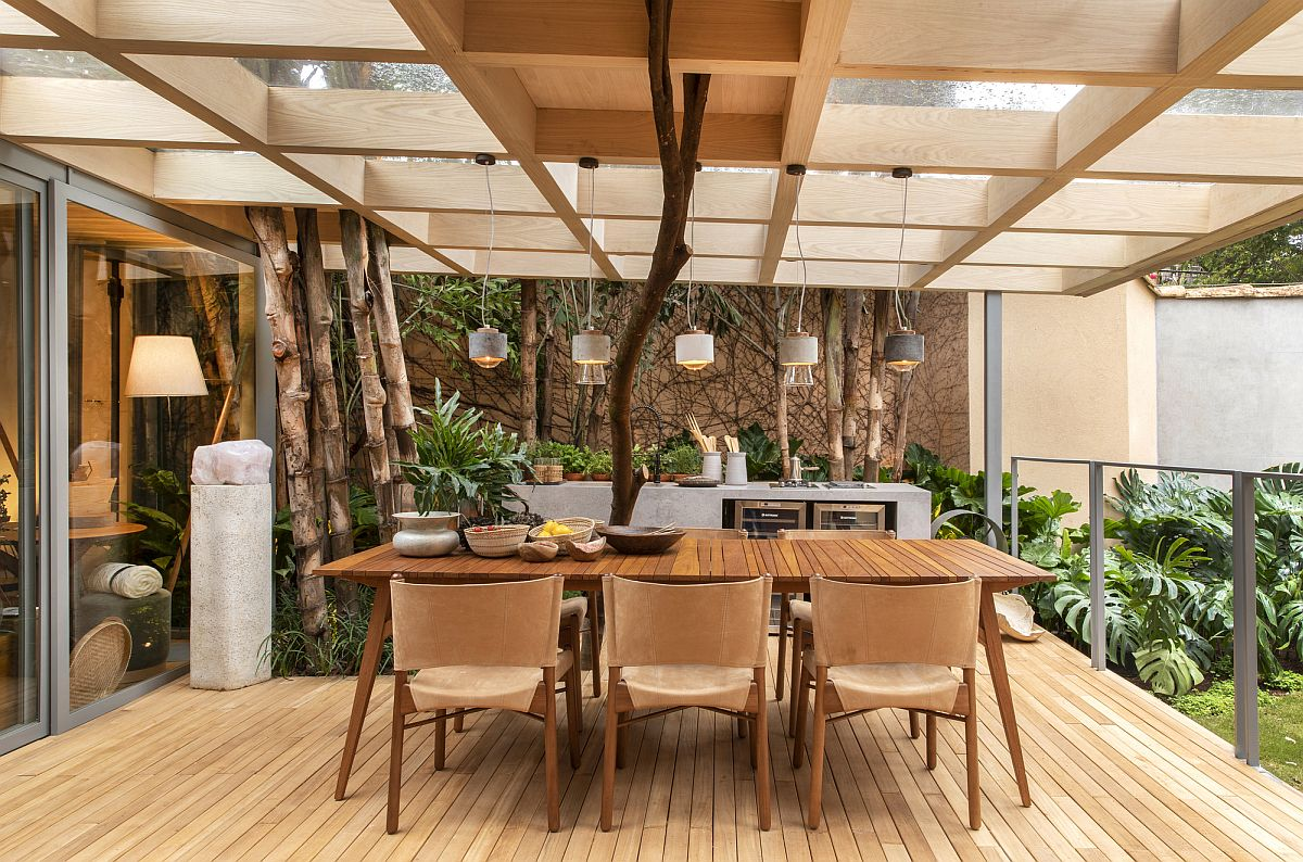 Picture-perfect outdoor dining area with pendant lights and a lovely wooden table that easily seats eight people