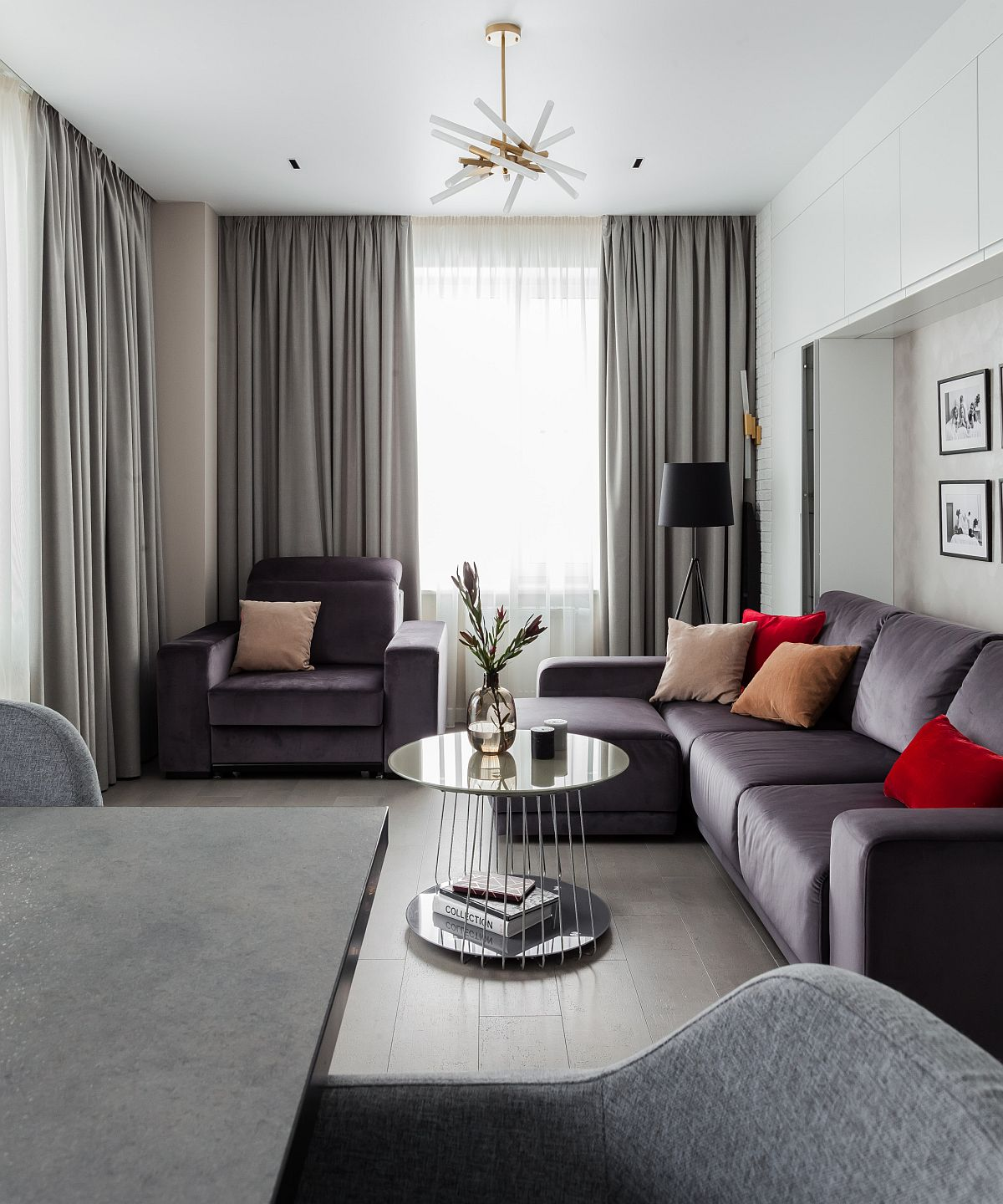 Sectional in gray adds to the color scheme of the tiny living room with red accents
