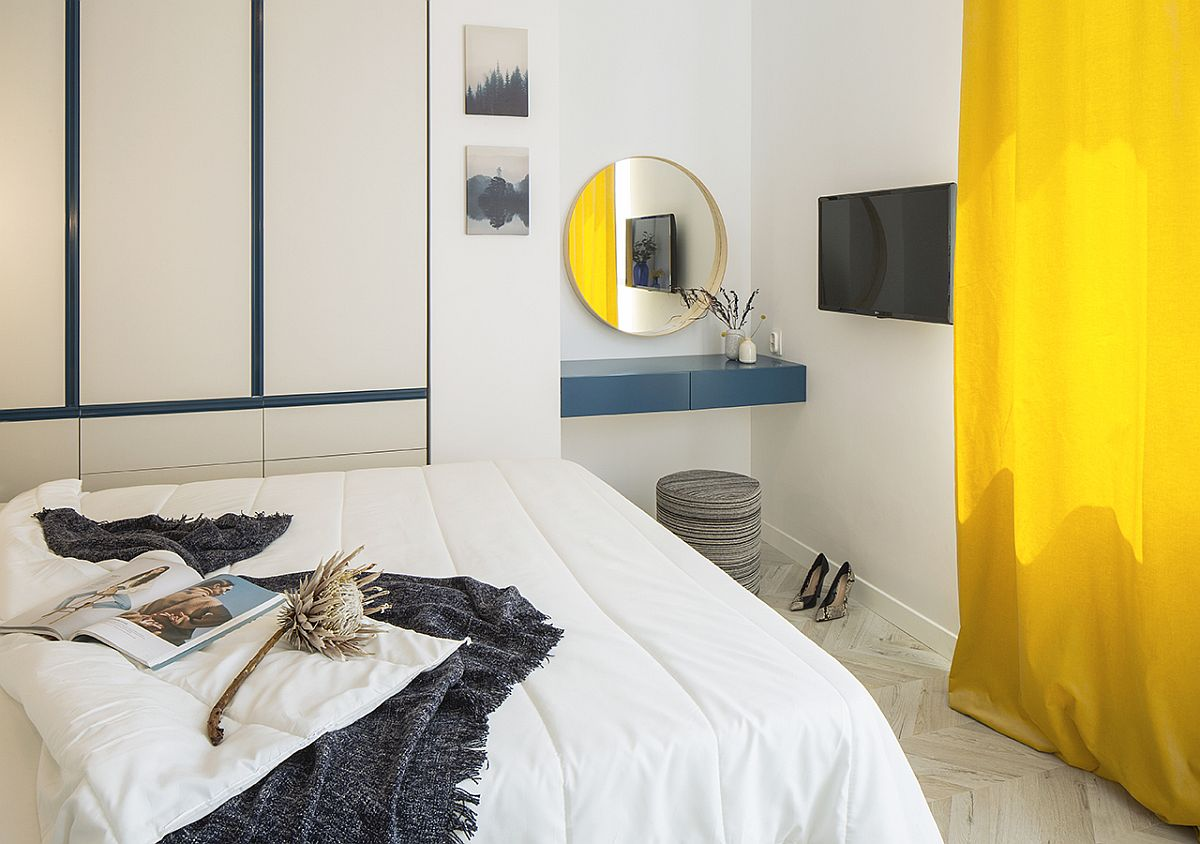 Simple floating dresser stand brings navy blue to the bedroom while the drapes add yellow