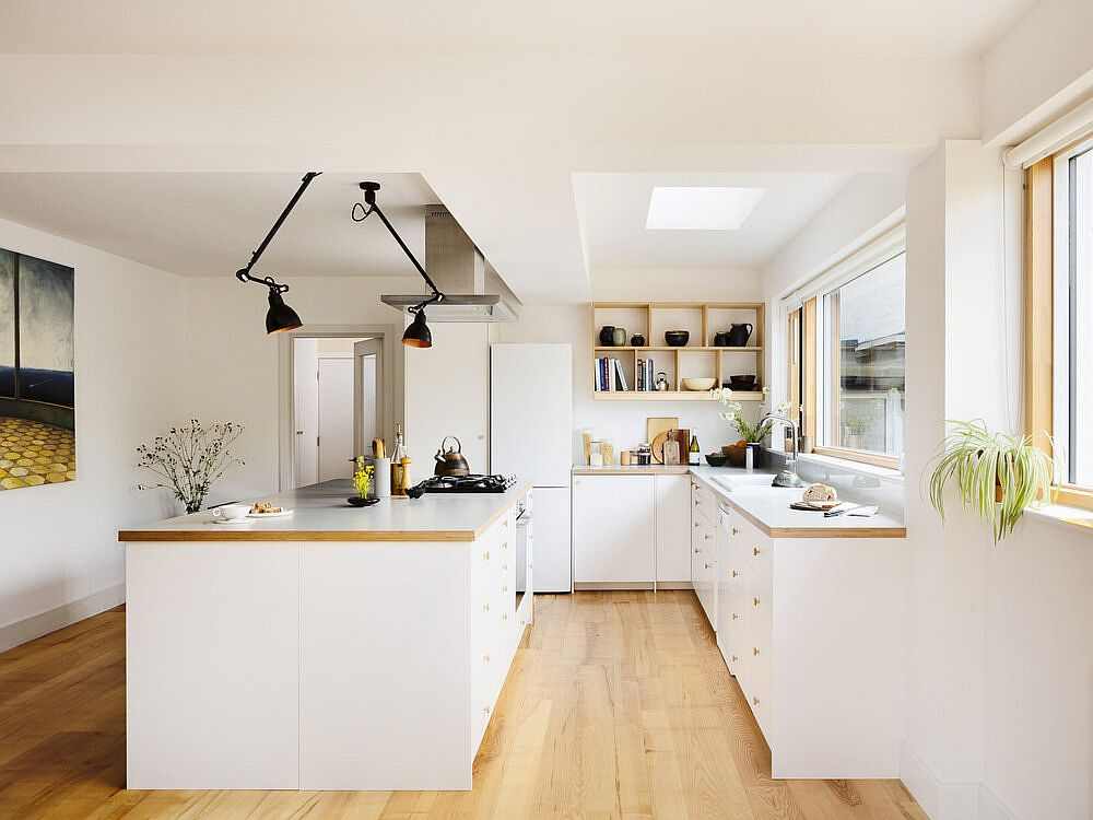 Skylight and sconce lights illuminate the white and wood kichen on the lower level elegantly