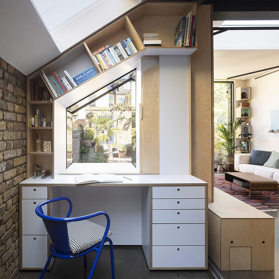 Slanted shelves and birch cabinets create a home workspace out of the tiny corner