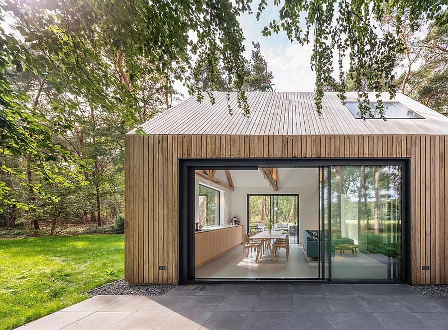 Sliding glass doors connect the interior of the cabin with the view outside
