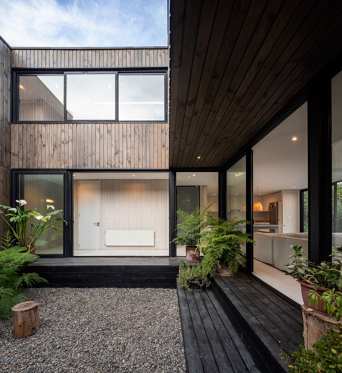 Sliding glass doors with steel frame and wood shape the exterior of the house