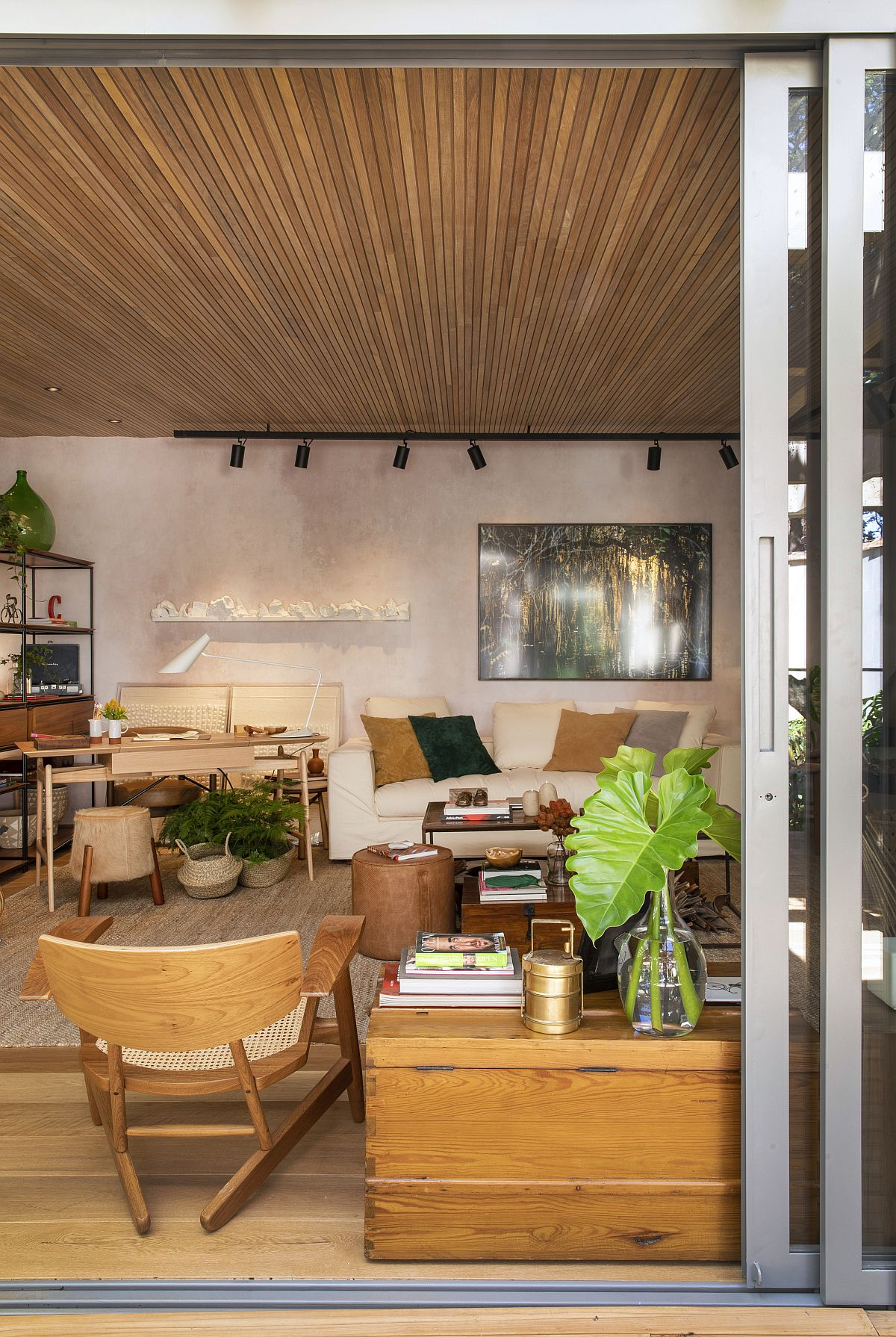 Sliding glass doors with wooden frame delineate the interior from the wooden deck ouside