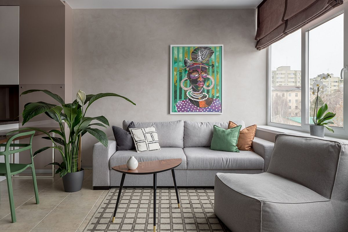 Small and trendy eclectic living room in gray where accent pillows and wall art usher in color