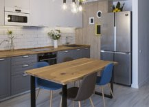 Small-eat-in-kitchen-with-wooden-dining-table-and-Edison-bulb-lighting-above-97650-217x155