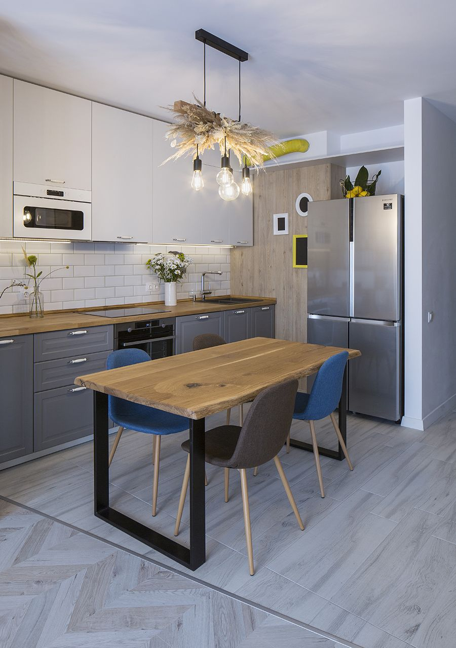 Small eat-in kitchen with wooden dining table and Edison bulb lighting above