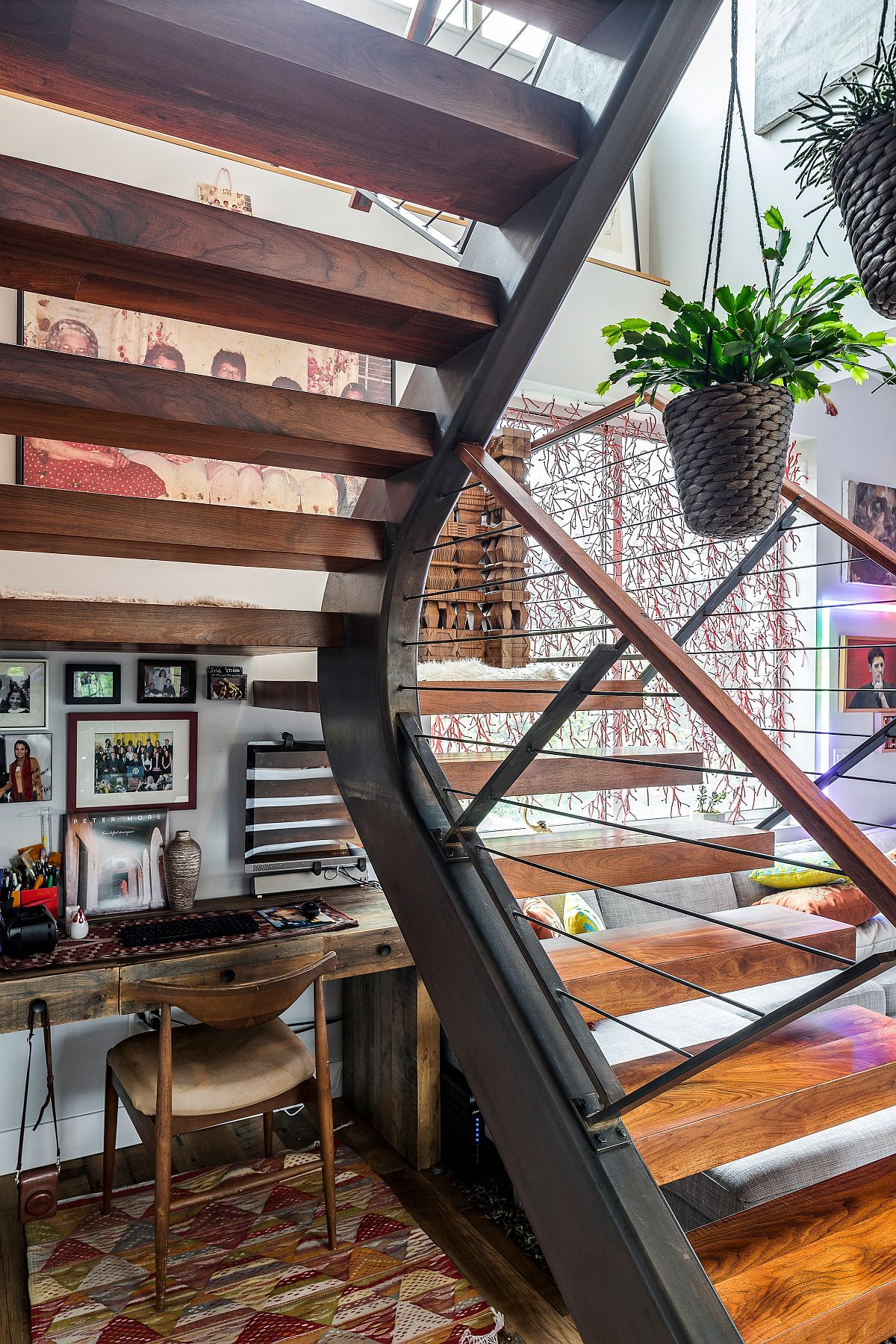 Small eclectic workspace under the staircase crafted using a simple wooden desk