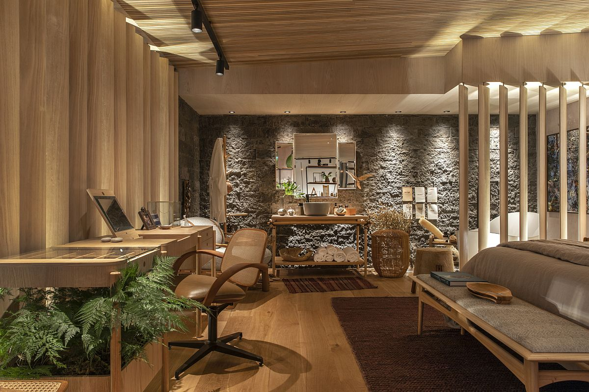 Smart lighting, stone wall, wooden finsihes and natural textures shape this lovely bedroom with home workspace