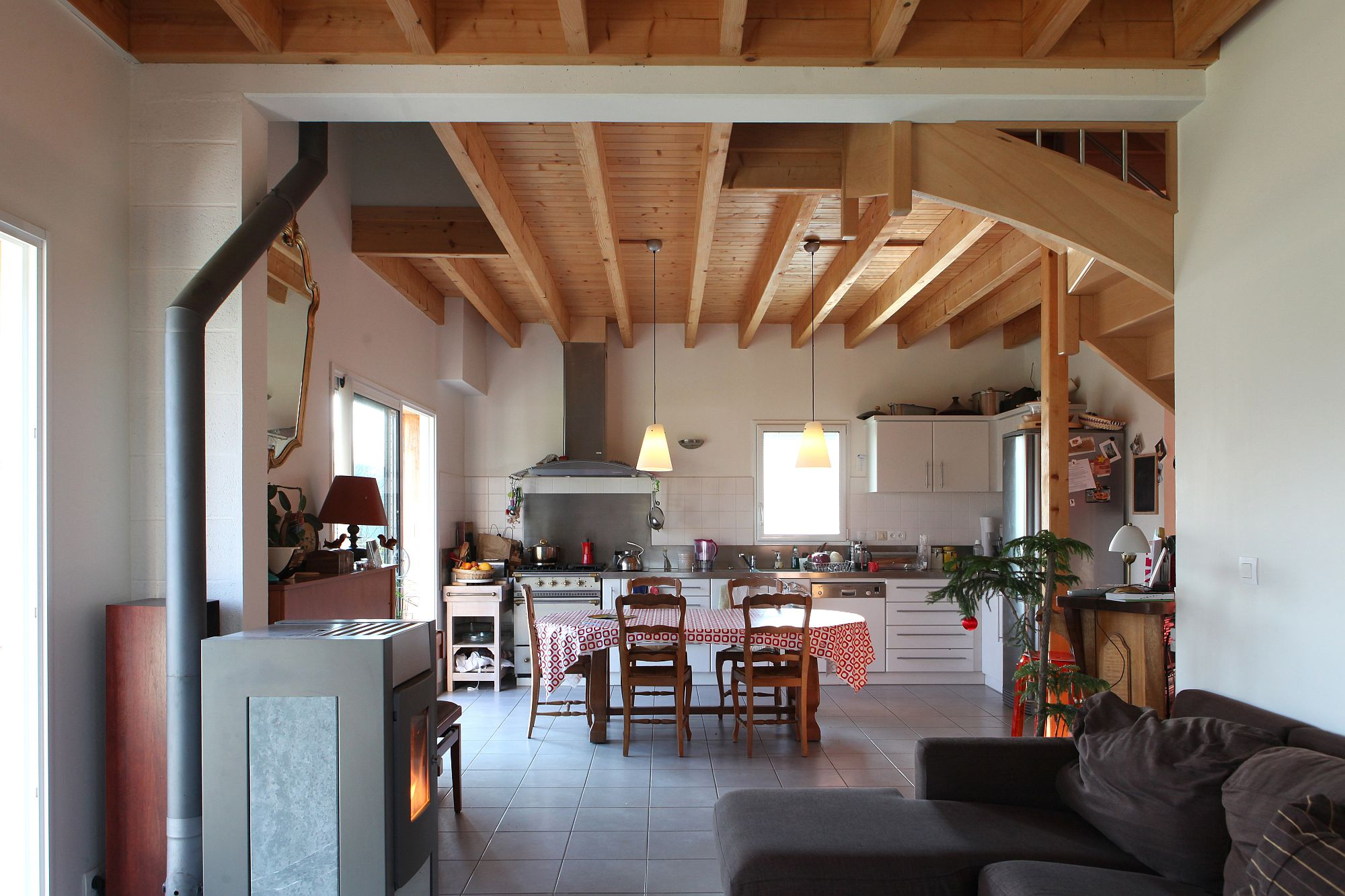 Social dining area and kitchen of he house with vernacular French cabin look