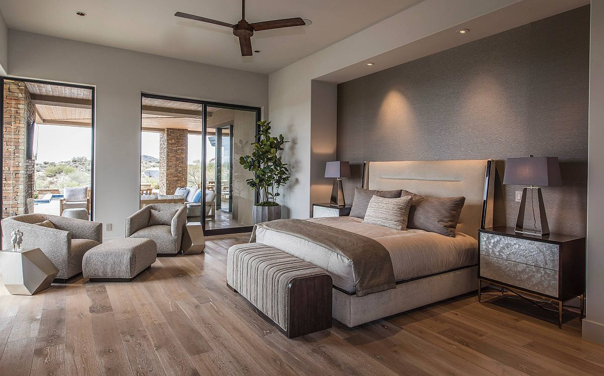Spacious bedroom of home in Phoenix with a textured gray accent wall, wooden floor and striking bedside lamps