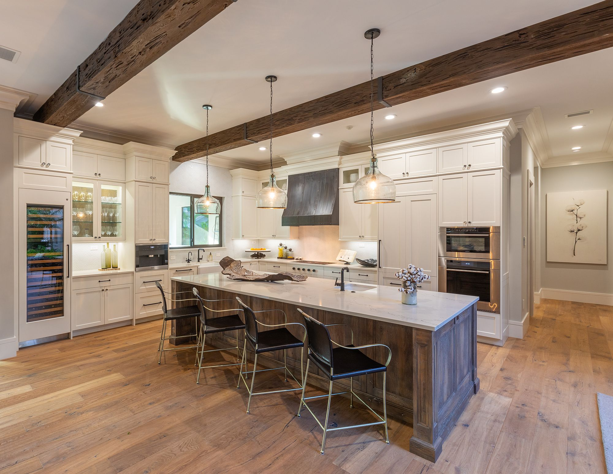 Spacious wood and white kitchen of the house with wooden ceiling beam and ample natural light