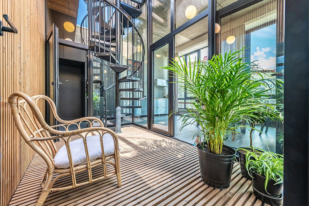 Spiral staircase connects the studio space on the lower level with the lovely modern-industrial apartment above