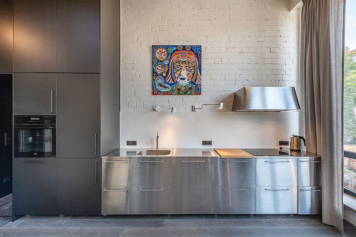 Stainless steel appliances and cabinets bring metallic gloss to the kitchen with white brick wall
