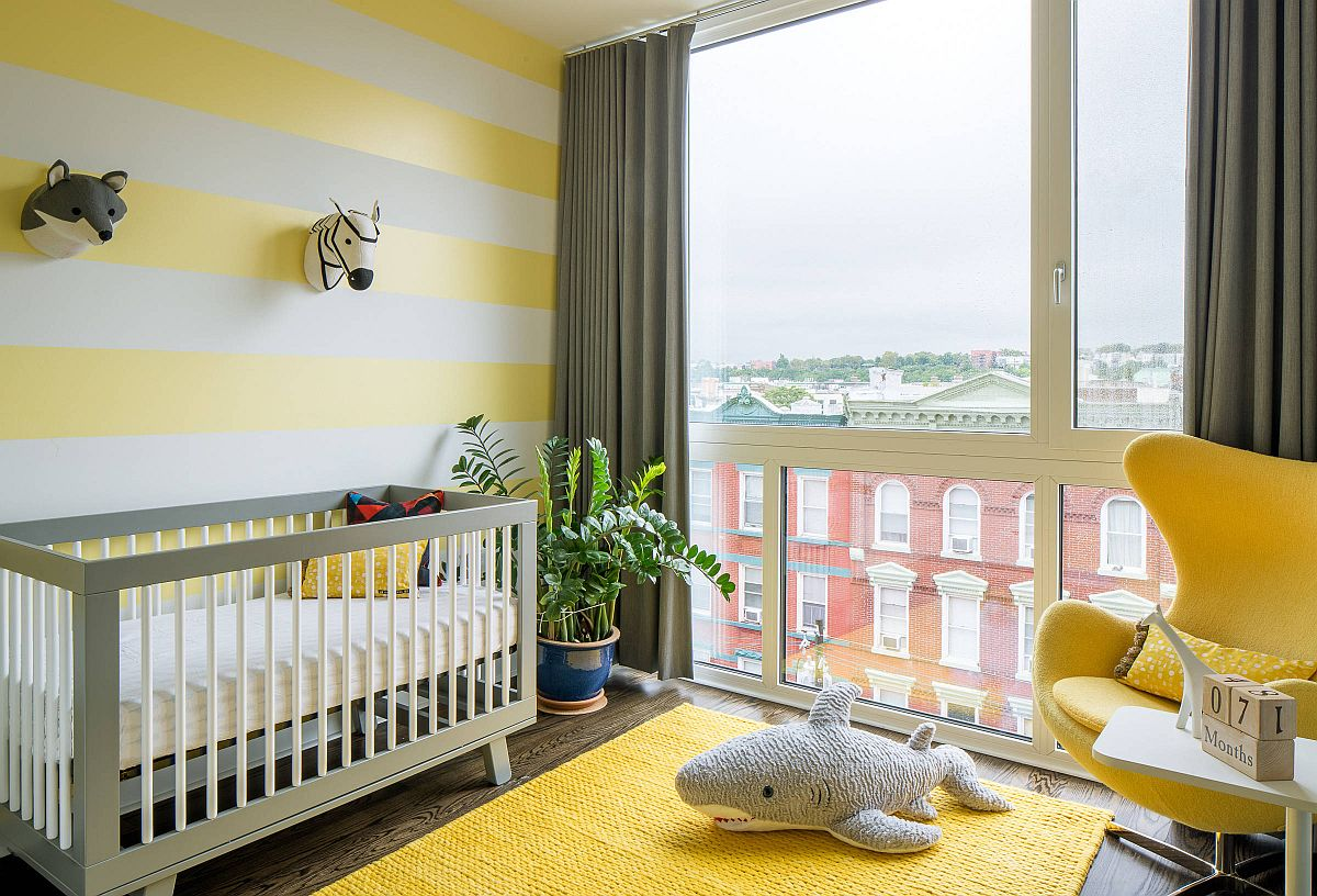 Striped accent wall in yellow and white along with yellow rug and chair in the smart modern nursery