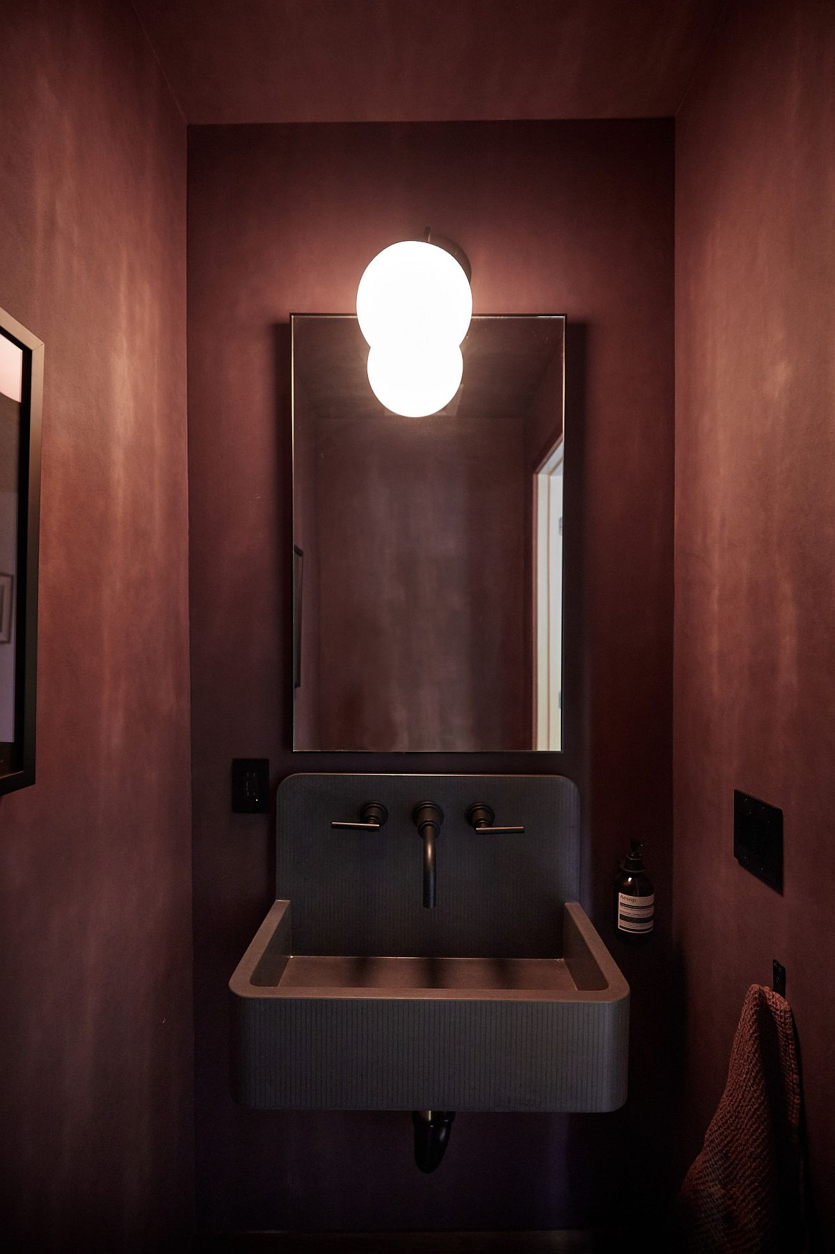 Textured walls in deep red create a sophisticated atmosphere inside the small powder room